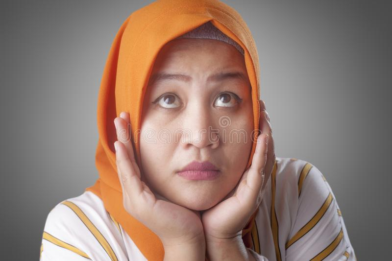 Muslim Businesswoman Thinking Something, Hand Under Chin. Asian muslim businesswomen wearing hijab with curiousity thinking expression. Looking for solution of a royalty free stock photos