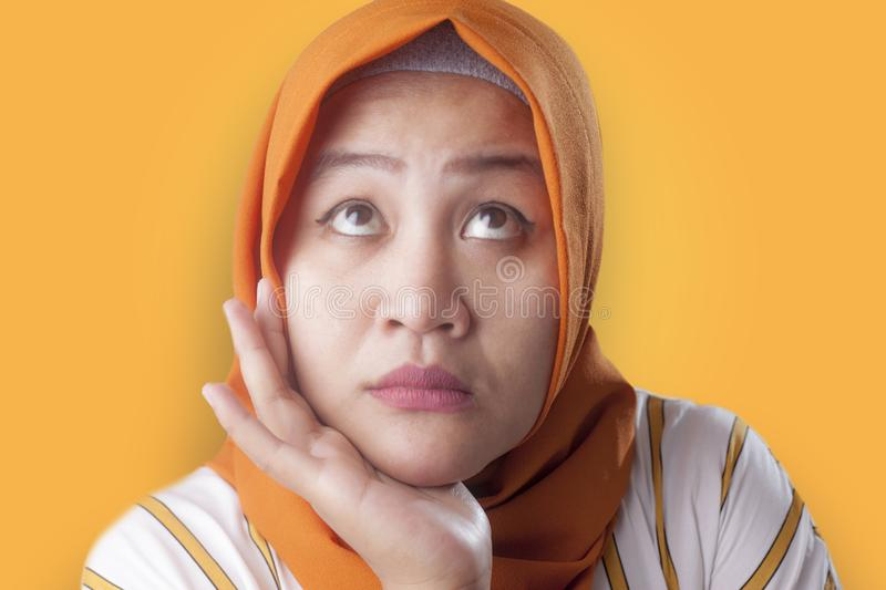 Muslim Businesswoman Thinking Something, Hand Under Chin. Asian muslim businesswomen wearing hijab with curiousity thinking expression. Looking for solution of a stock photography