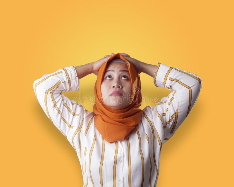 Muslim Businesswoman Thinking Something, Hands Behind Head. Asian muslim businesswomen wearing hijab with curiousity thinking expression. Looking for solution of royalty free stock photography