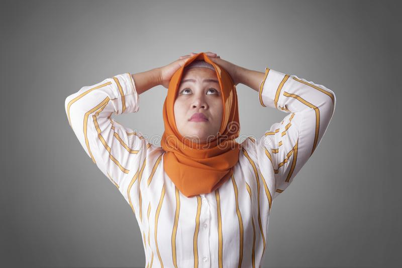 Muslim Businesswoman Thinking Something, Hands Behind Head. Asian muslim businesswomen wearing hijab with curiousity thinking expression. Looking for solution of royalty free stock photo
