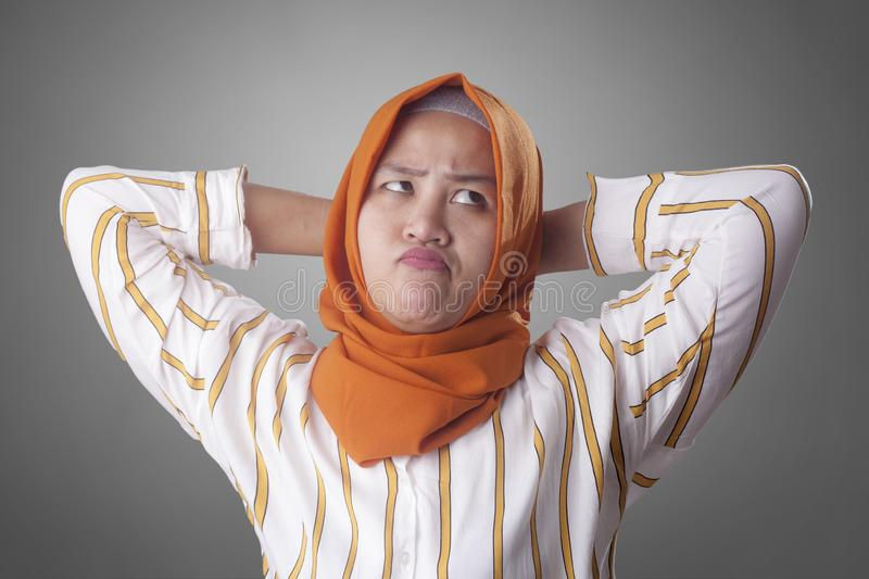 Muslim Businesswoman Thinking Something, Hands Behind Head. Asian muslim businesswomen wearing hijab with curiousity thinking expression. Looking for solution of stock image