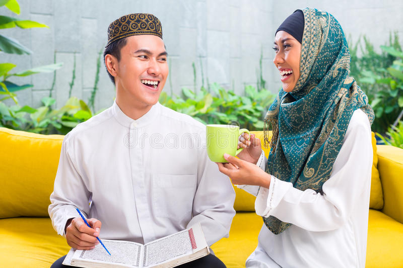 Asian Muslim couple drinking coffee or tea royalty free stock images