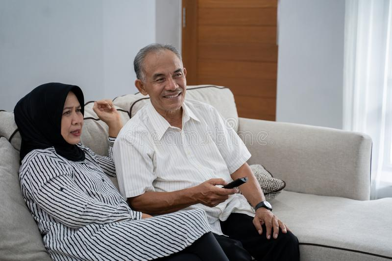 Asian muslim couple mature sitting couch relaxed when enjoy television stock photography