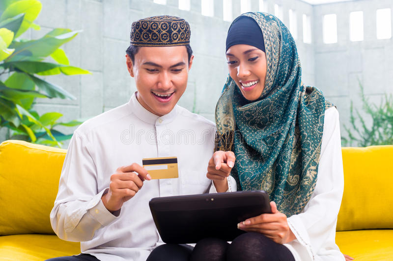 Asian Muslim couple shopping online on pad in living room. Asian Muslim men and women shopping online paying with credit card on tablet PC royalty free stock photo