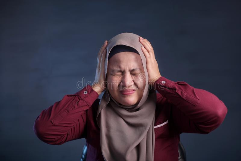 Asian Muslim Lady Close Her Ears. Portrait of Asian muslim lady wearing hijab close hear ears with hands as if do not want to hear something bad, indonesian royalty free stock images