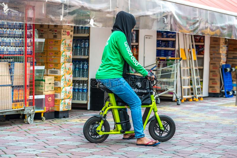 Asian Muslim Malay female with hijab food delivery rider on e-bike scooter. South East Asia / Singapore - Nov 9, 2019 Asian Muslim Malay female with hijab head stock photo
