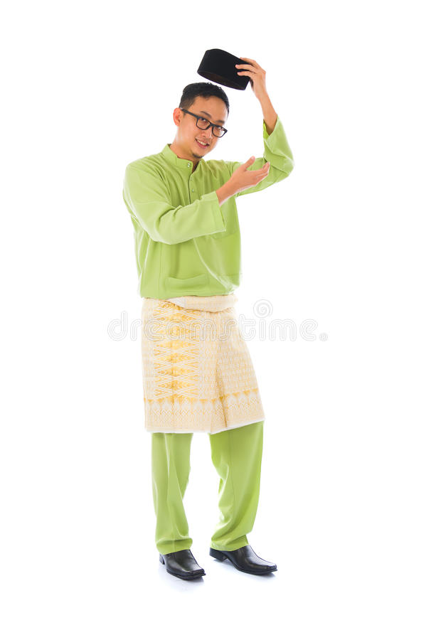Asian muslim male with traditional Malay costume in smiling action, Baju Melayu royalty free stock photography