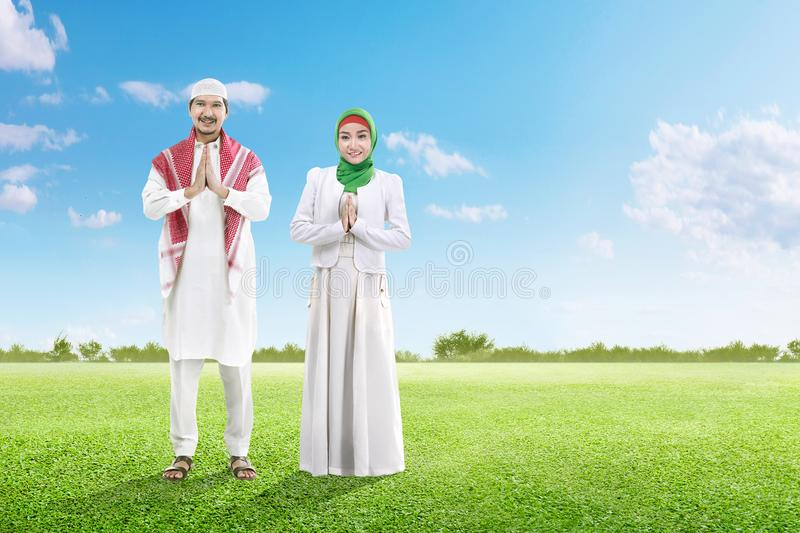 Asian muslim man with cap and muslim woman with veil praying together on the green grass field. Asian muslim men with cap and muslim women with veil praying stock images