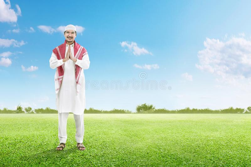Asian muslim man in cap praying on the green grass field. With blue sky background royalty free stock image