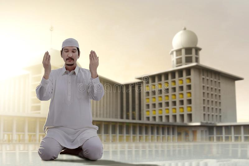 Asian Muslim man sitting in pray position while raised hands and praying. Outside the mosque stock photos
