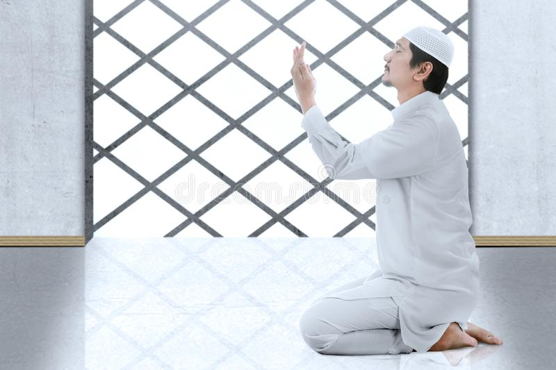 Asian Muslim man sitting in pray position while raised hands and praying. Inside the mosque stock photo