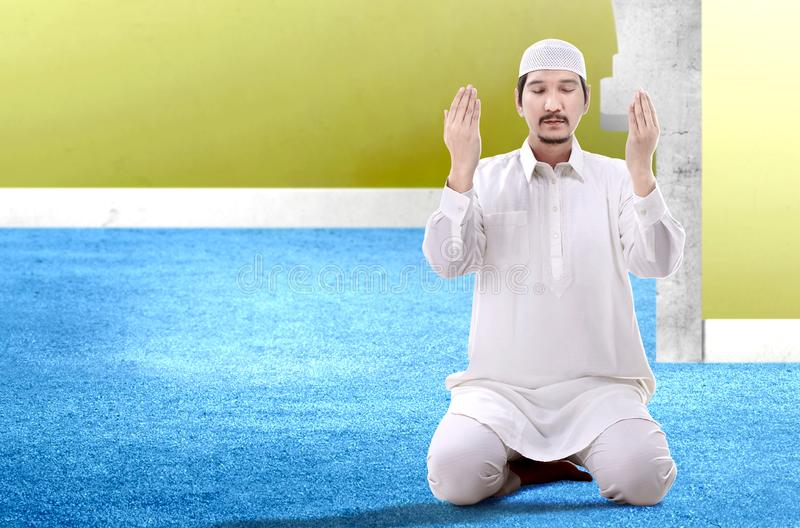 Asian Muslim man sitting in pray position while raised hands and praying. Inside the mosque stock photography