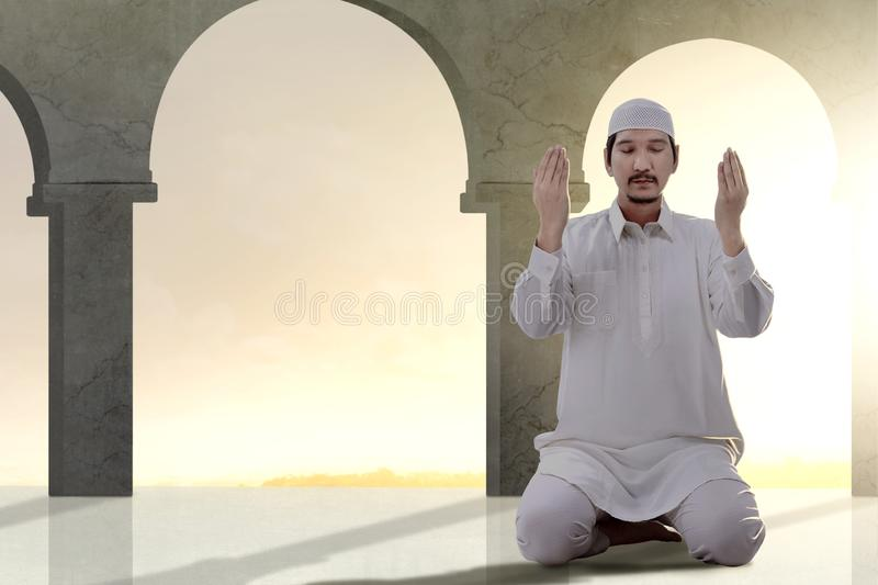 Asian Muslim man sitting in pray position while raised hands and praying. Inside the mosque royalty free stock images