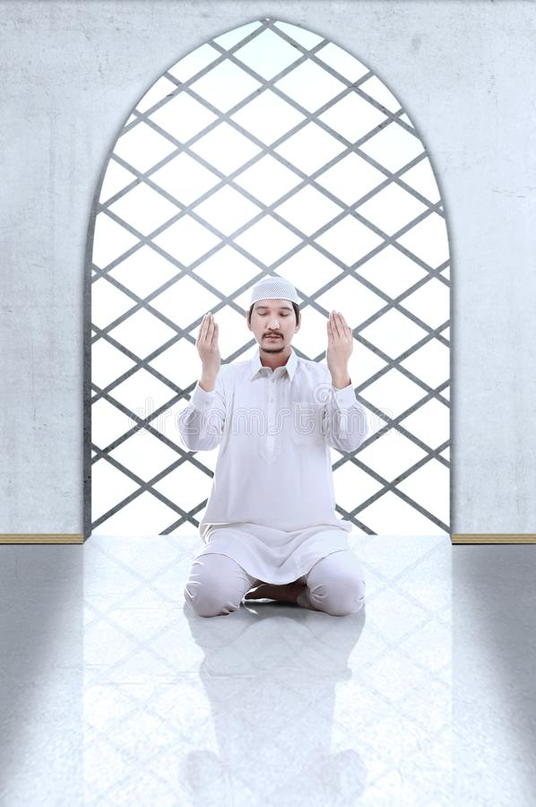 Asian Muslim man sitting in pray position while raised hands and praying. Inside the mosque royalty free stock photo