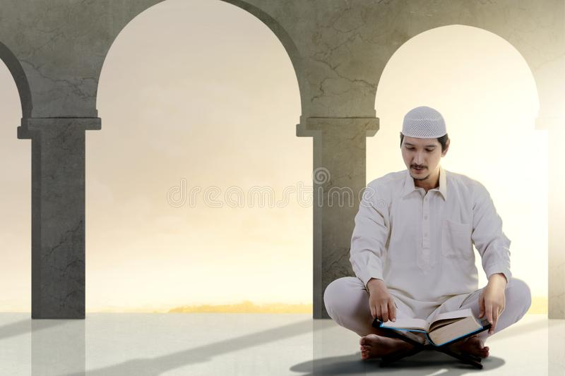 Asian Muslim man sitting and read the Koran. Inside the mosque stock photography