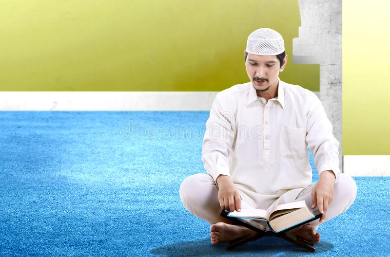 Asian Muslim man sitting and read the Koran. Inside the mosque stock photo