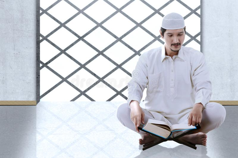 Asian Muslim man sitting and read the Koran. Inside the mosque royalty free stock photography