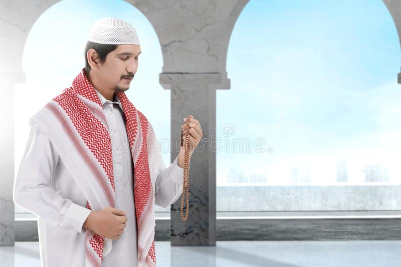 Asian Muslim man standing and praying with prayer beads. Inside the mosque royalty free stock photos