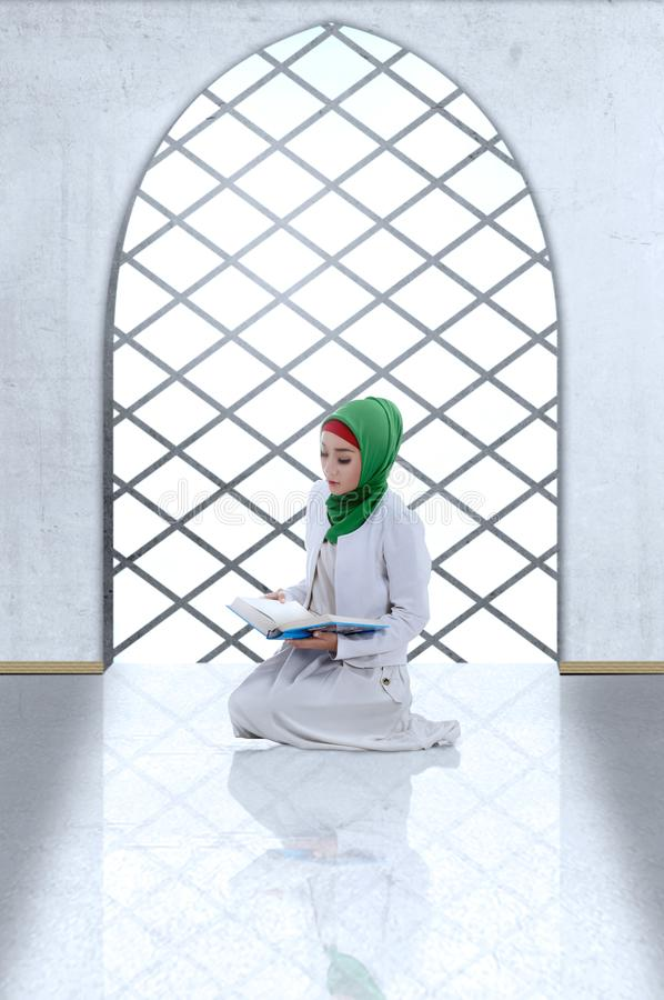 Asian Muslim woman in veil sitting and read the Koran. Inside the mosque royalty free stock images