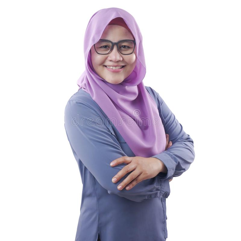 Muslim woman Smiling Friendly With Crossed Arms. Asian muslim woman wearing blue shirt and purple hijab smiling friendly with arms crossed, confident successful royalty free stock photography