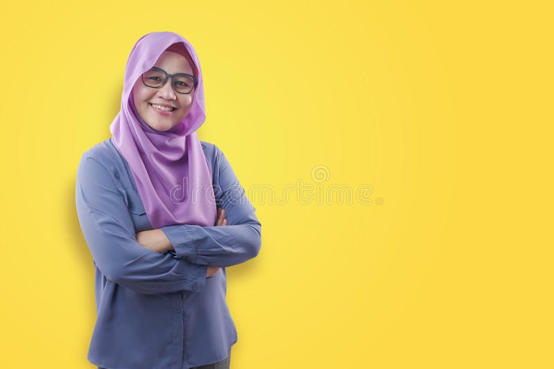 Muslim woman Smiling Friendly With Crossed Arms. Asian muslim woman wearing blue shirt and purple hijab smiling friendly with arms crossed, confident successful royalty free stock photos