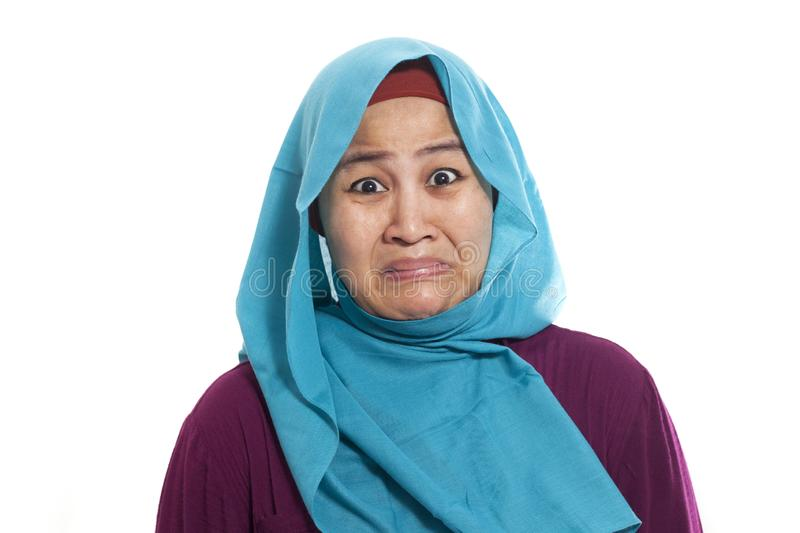 Asian muslim woman wearing hijab showing a ridiculous expression, absurd. Isolated on white. Close up head and shoulders stock image