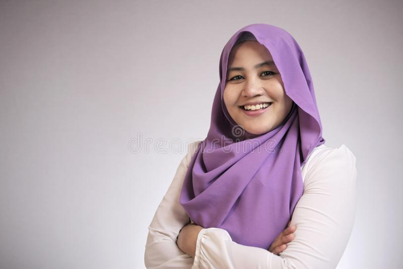 Muslim Lady Smiling Friendly. Asian muslim woman wearing hijab smiling friendly with arms crossed against gray background, female, businesswoman, arab stock photo