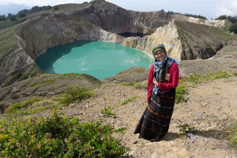 An Asian Muslim woman wearing a hijab is taking a photo in front of a green view of the Kelimutu-Flores lake royalty free stock photo