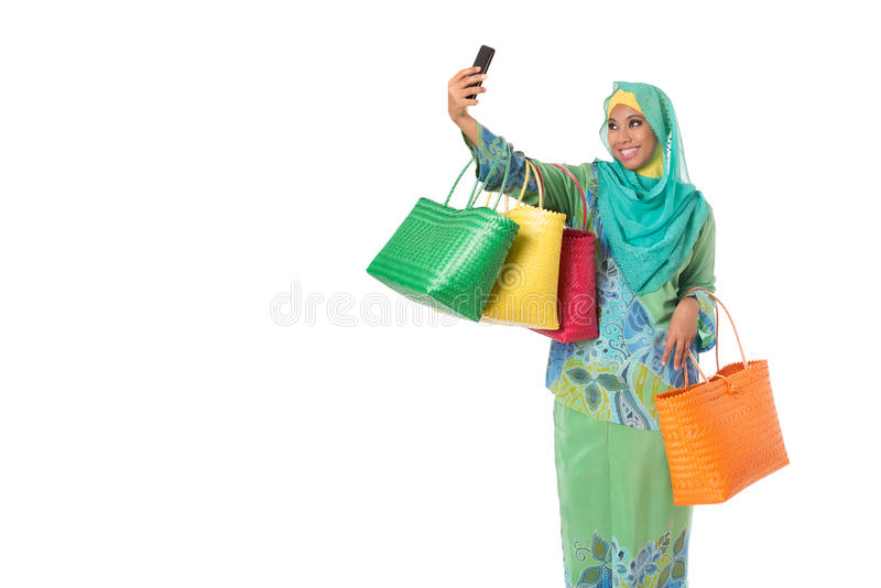 Asian muslimah woman with bright wicker tote bags taking selfie. royalty free stock photography