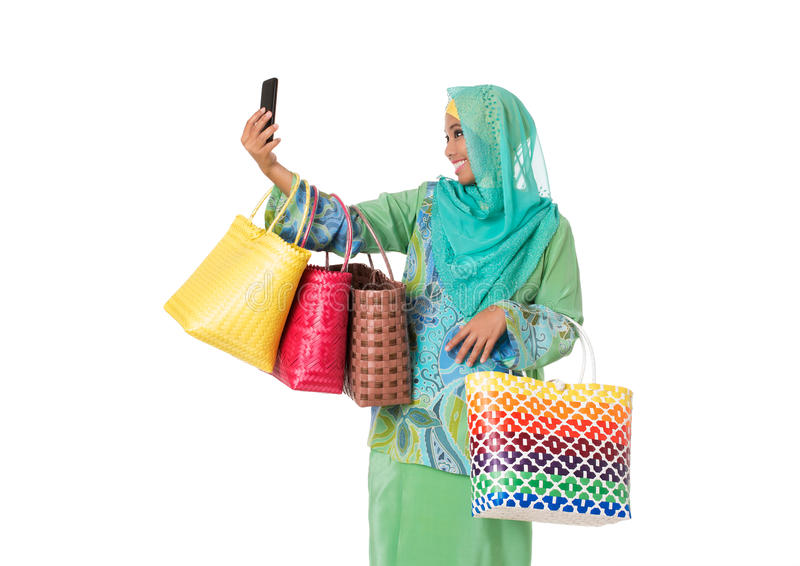 Asian muslimah woman with bright wicker tote bags taking selfie.Isolated royalty free stock photography