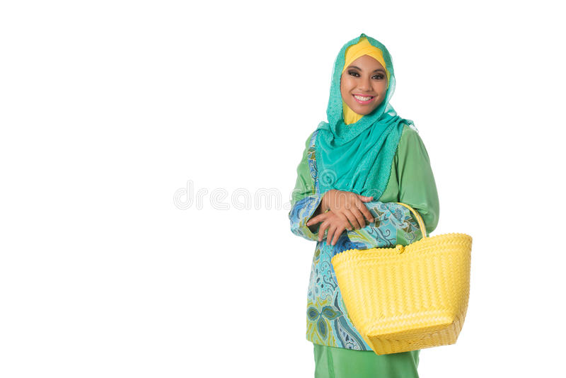 Asian muslimah woman with wicker tote bag.Isolated.Copyspace. Beautiful asian muslimah woman with yellow wicker tote bag. Isolated on the white studio background stock image