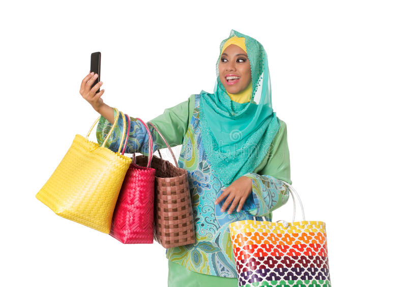 Asian muslimah woman with wicker tote bags taking selfie.Isolated royalty free stock image