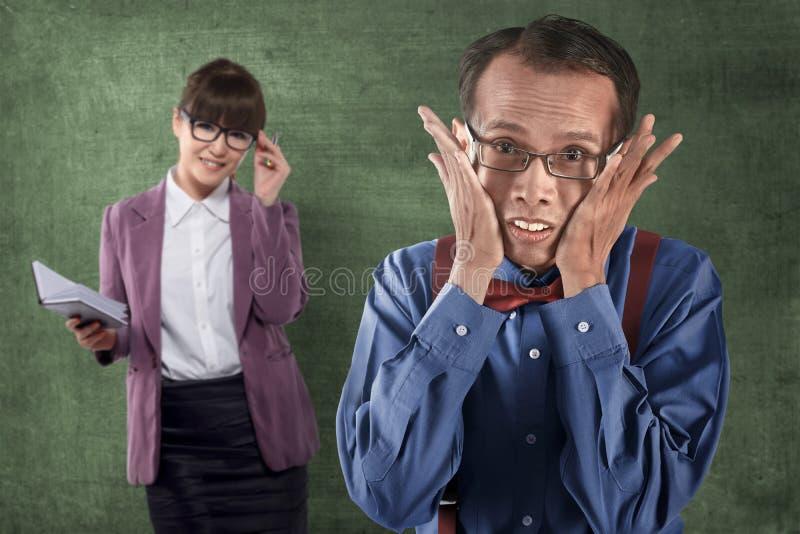 Asian nerd man looking shy with beautiful teacher behind him royalty free stock photos