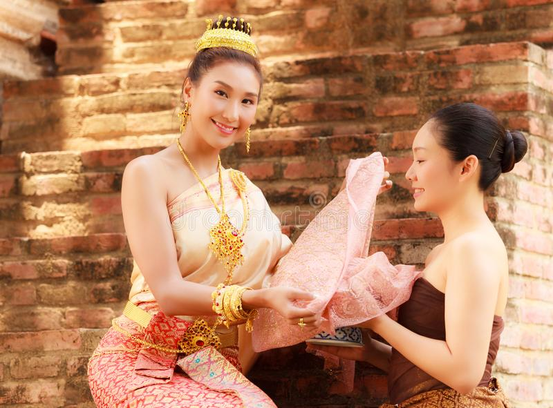 Asian noble beauty with maid dressed in traditional clothes shopping in old retro historical period theme.  stock photos
