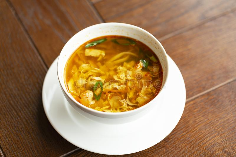 Asian noodle soup with chicken, vegetables and egg in a bowl on a wooden table. royalty free stock images