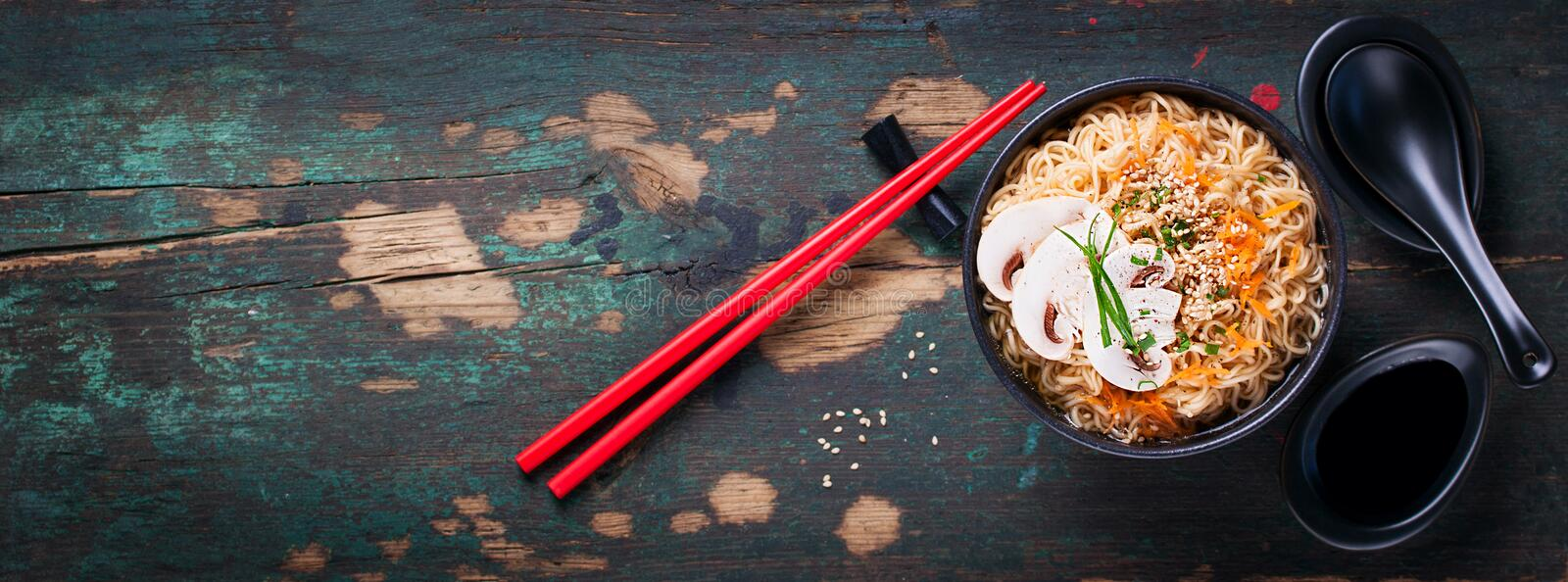 Asian noodles with vegetables and mushrooms, soy sauce, sticks on a dark background royalty free stock photo