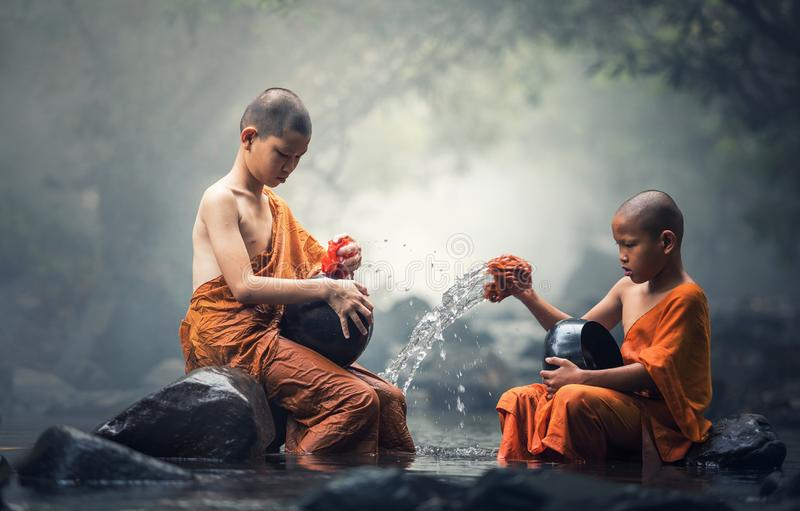 Asian Novice monks cleaning alms bowl. In creeks royalty free stock photos