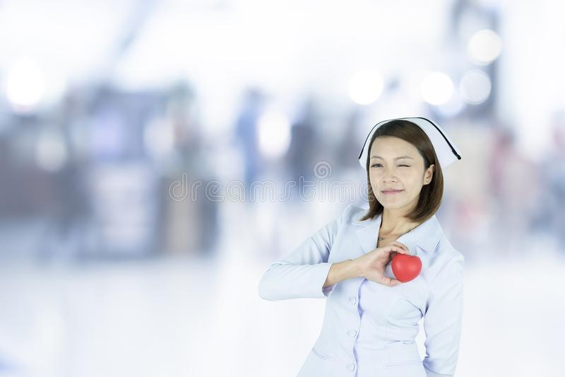 Asian nurse is holding a red heart shape on hospital blurred background. stock photo
