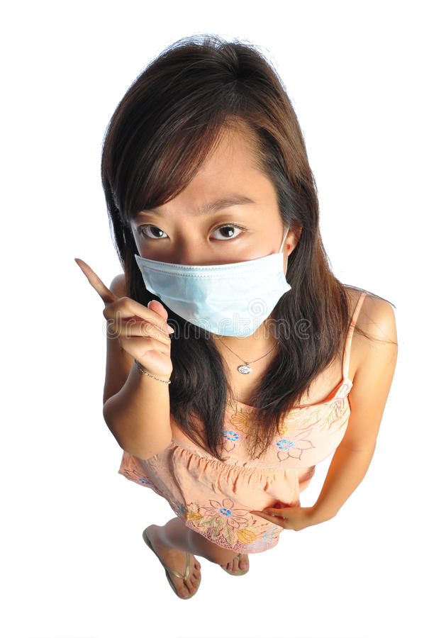Asian nurse with mask being strict. Beautiful young Asian Woman nurse picture taken from the top to give a big doll head effect royalty free stock image
