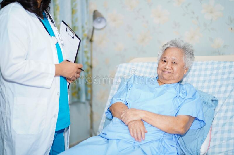 Asian nurse physiotherapist doctor care, help and support senior or elderly old lady woman patient at hospital stock images
