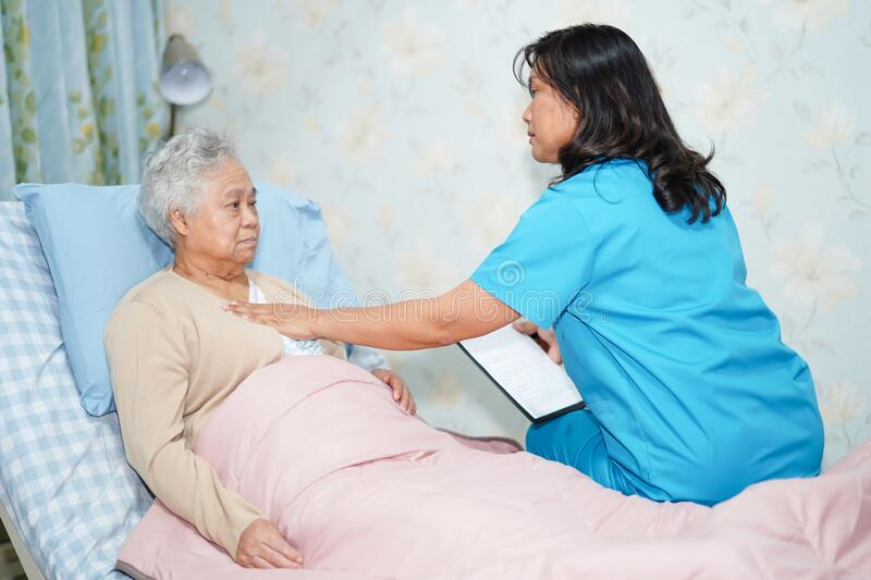 Asian nurse physiotherapist doctor care, help and support senior or elderly old lady woman patient stock image