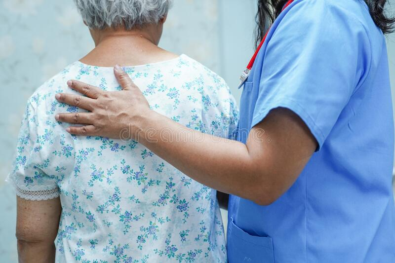 Asian nurse physiotherapist doctor touching Asian senior or elderly old lady woman patient with love, care, helping, royalty free stock images