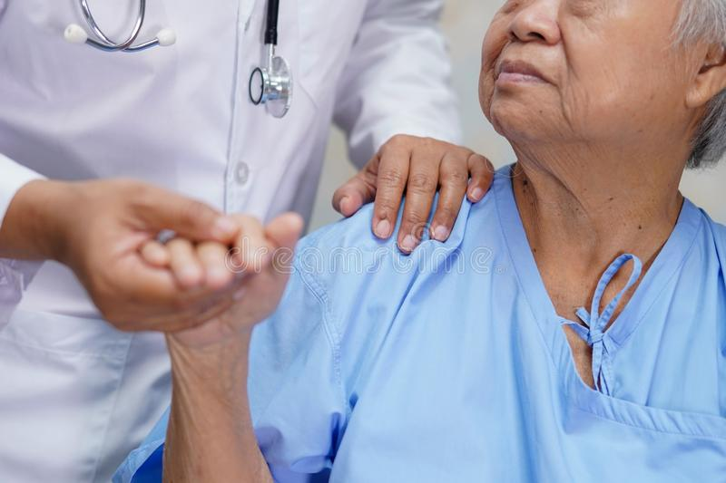 Asian nurse physiotherapist doctor touching Asian senior or elderly old lady woman patient with love stock image