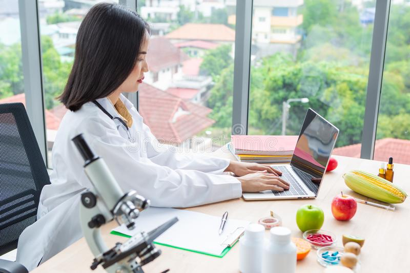 Asian nutritionist doctor woman working labtop with microscope on wooden table. In laboratory room royalty free stock photos