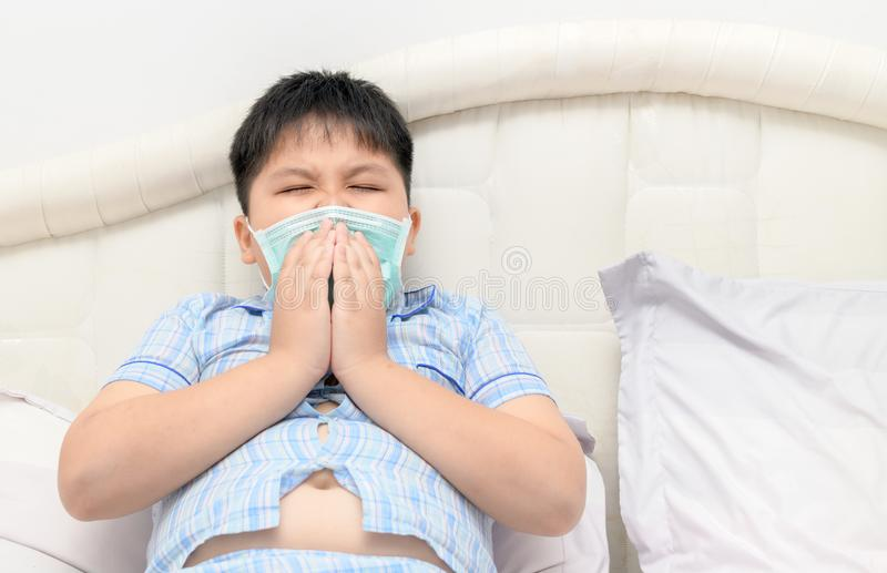 Asian obese fat boy sneeze with face mask protection stock photo