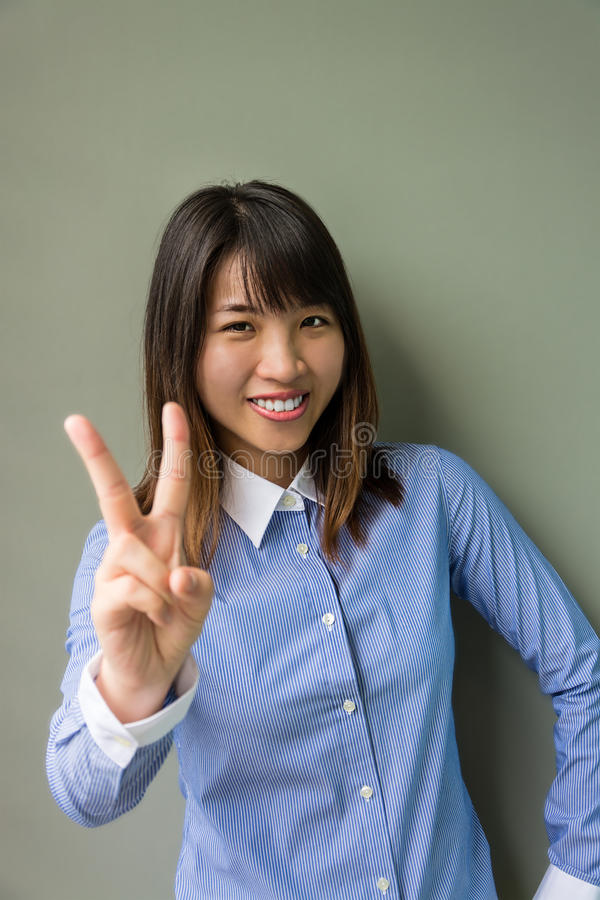 Download Asian Office Girl Showing Victory Sign In Grey Background Stock Photo - Image: 30556080