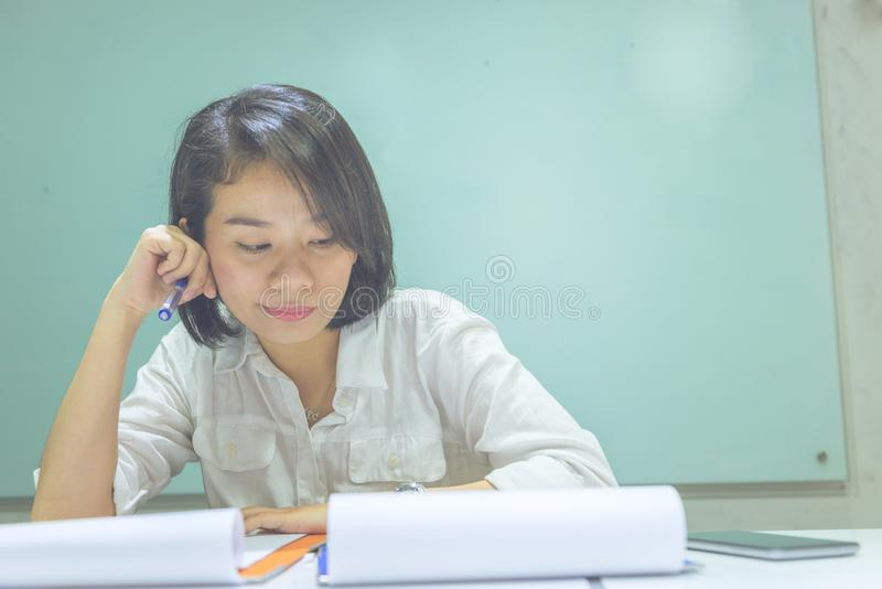 Asian office woman reading information on sales report stock images