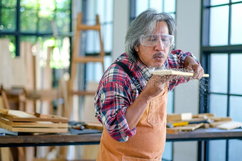 Asian old craftsman blow some sliver after cut the wood. He also wear protected glass and work in room surround with glasses royalty free stock image
