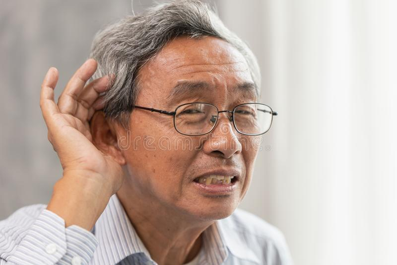 Old man with Deaf Hearing problems. Asian old man with Deaf Hearing problems place hand on ear for help listening louder stock photo