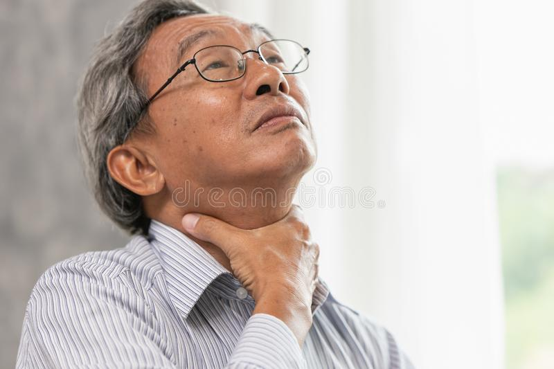 Asian old man sore throat irritation hand massage squeeze at neck. Asian old man elderly sore throat irritation hand massage squeeze at neck stock image